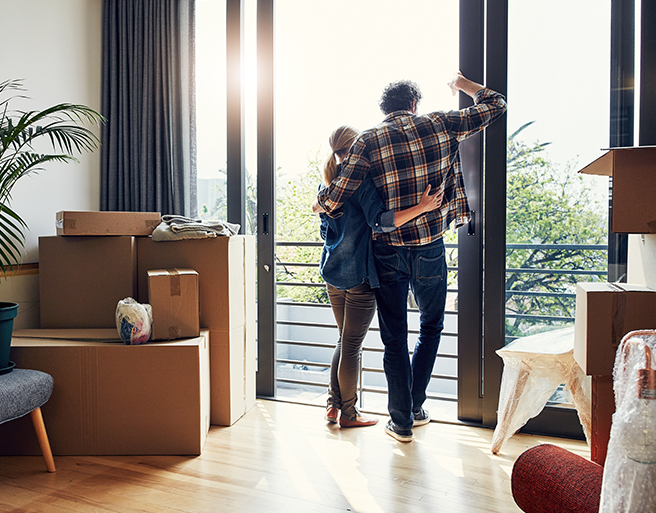 middle aged couple surrounded by moving boxes in new condo